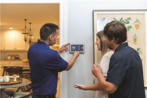 Homeowners setting thermostat